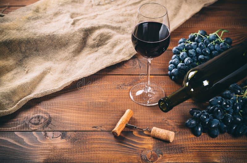 瓶和杯红葡萄酒,葡萄, 免版税图库摄影