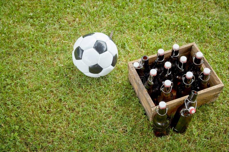 瓶在一个足球旁边的啤酒在草 库存照片