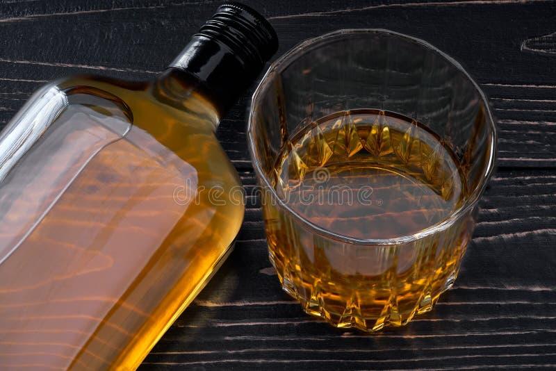瓶在一张黑木桌上的威士忌酒 顶视图 免版税库存图片
