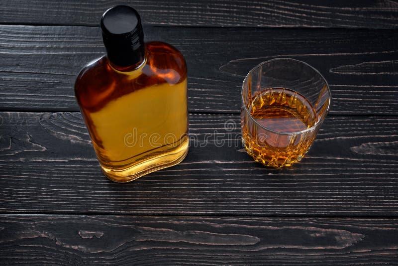 瓶在一张黑木桌上的威士忌酒 顶视图 免版税库存照片