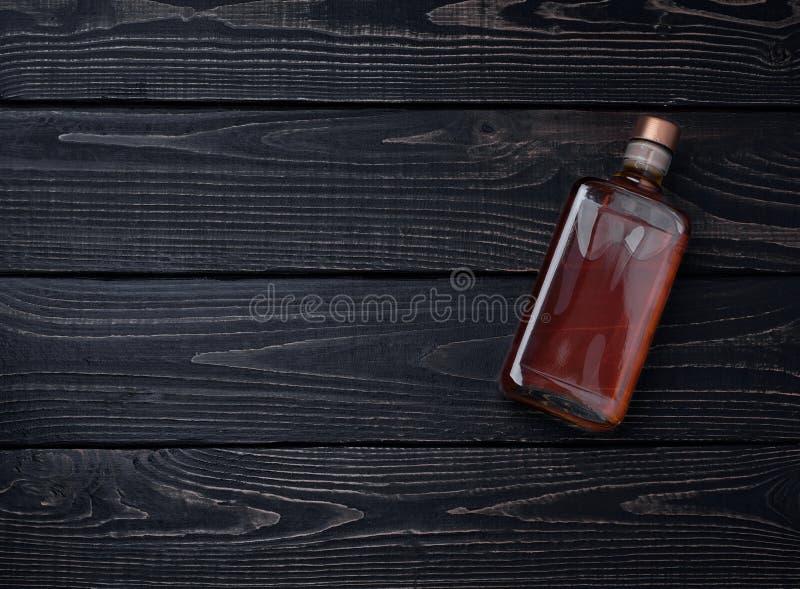 瓶在一张黑木桌上的威士忌酒 顶视图 库存照片