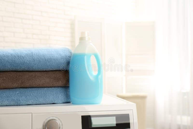 瓶在户内洗衣机的洗涤剂和清洁毛巾,文本的空间 免版税图库摄影