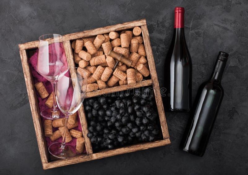 瓶在木头与空的玻璃和黑暗的葡萄与黄柏和拔塞螺旋的红酒在黑暗木的葡萄酒木箱里面 库存照片