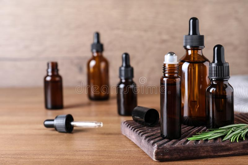 瓶在木桌上的迷迭香精油 免版税图库摄影