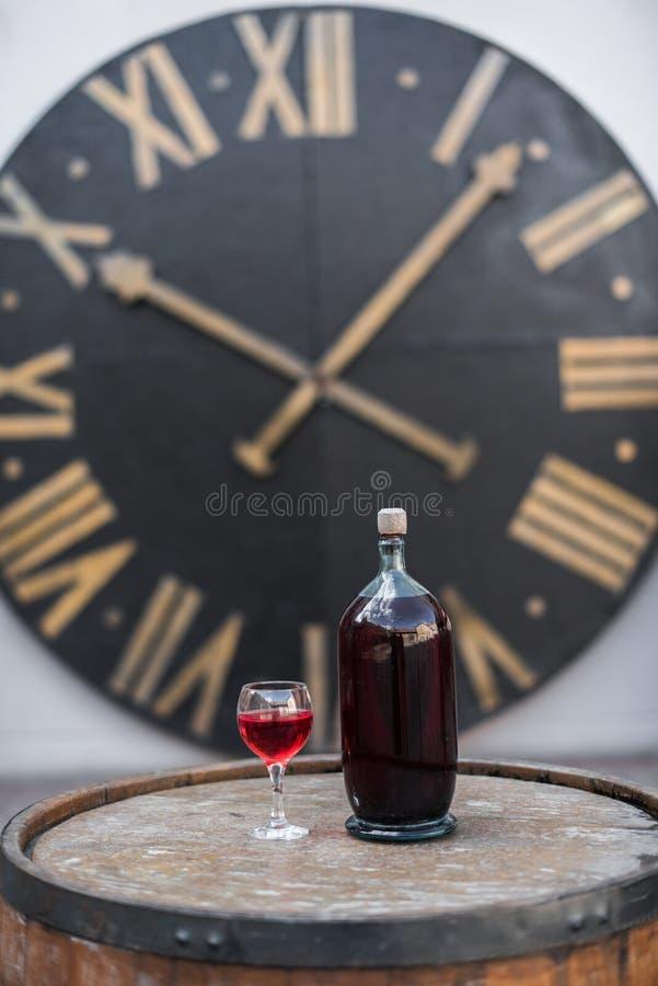 瓶在木桶的红葡萄酒 古老时钟背景 免版税库存照片