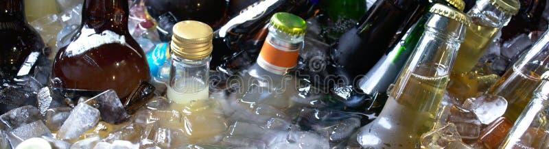 瓶在桶的冷的饮料与冰在热的夏日 免版税库存照片