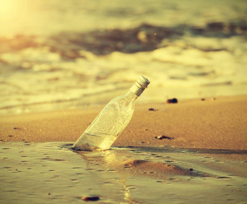 瓶在海滩的水中在日落,减速火箭的instagram作用 免版税库存图片