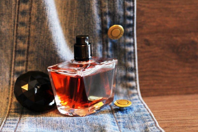 瓶在牛仔裤的香水,木背景 免版税库存照片