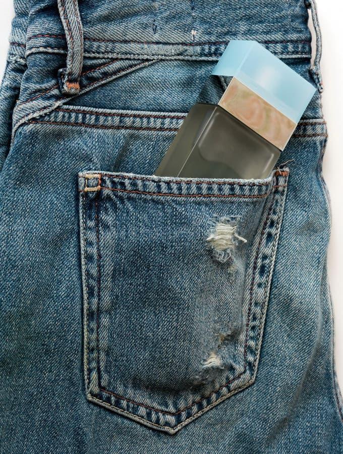 瓶在牛仔裤的香水 免版税库存图片