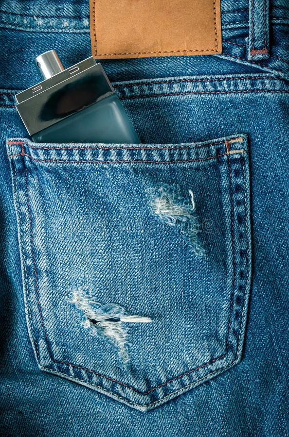 瓶在牛仔裤的香水 免版税库存照片