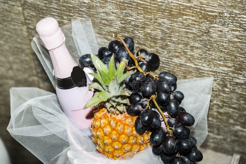 瓶在篮子的桃红色闪耀的香槟用果子 免版税库存照片