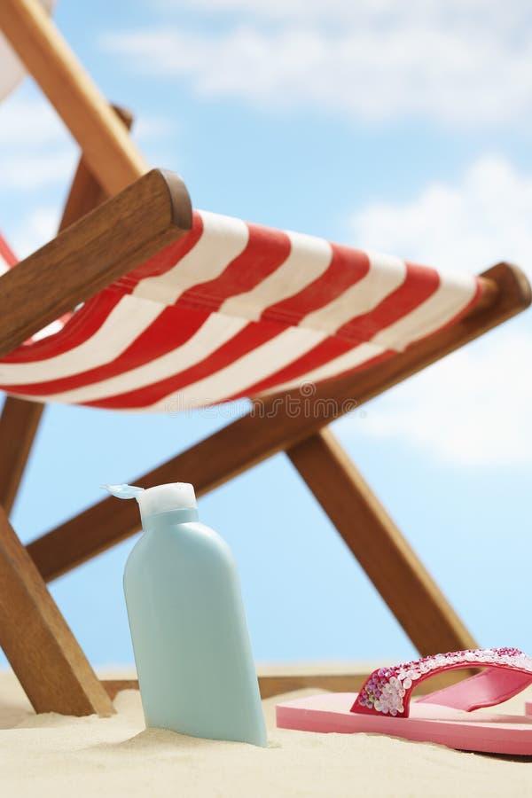 瓶在deckchair下的奶油色化妆水在海滩 库存图片