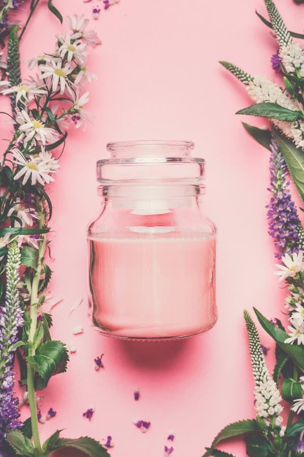 瓶子与花和草本,顶视图的桃红色自然化妆奶油 自然草本化妆产品 库存图片