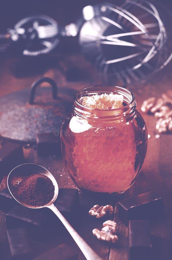 瓶子与里面蜂窝的健康真正的蜂蜜,巧克力毁损 免版税库存图片