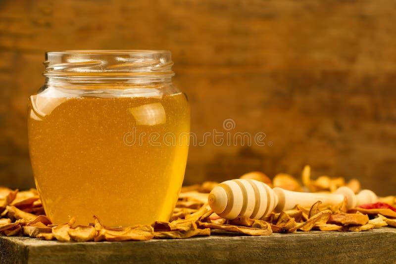 瓶子与drizzler的新鲜的蜂蜜,用在木背景的干苹果 库存照片