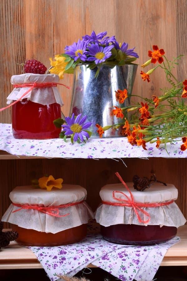 瓶子另外果酱和一个金属水罐有花的 库存图片