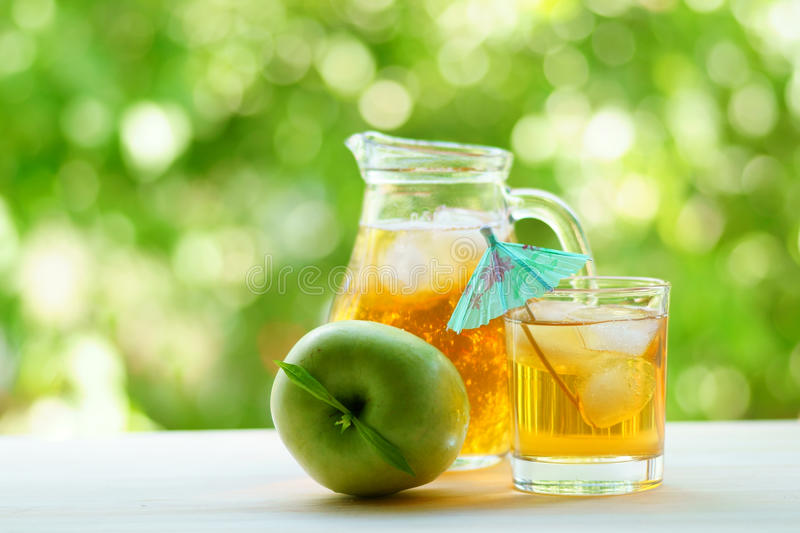 瓶子和玻璃有很多与冰,绿色苹果的新鲜的苹果汁 库存照片