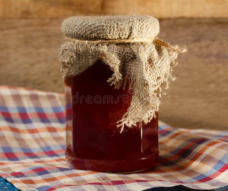 瓶子在木墙壁的背景的果酱 免版税库存图片