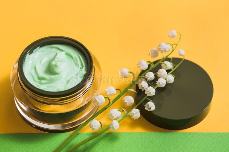 瓶子春黄菊与春黄菊的面霜开花与选择聚焦 化妆用品桃红色背景 免版税库存图片