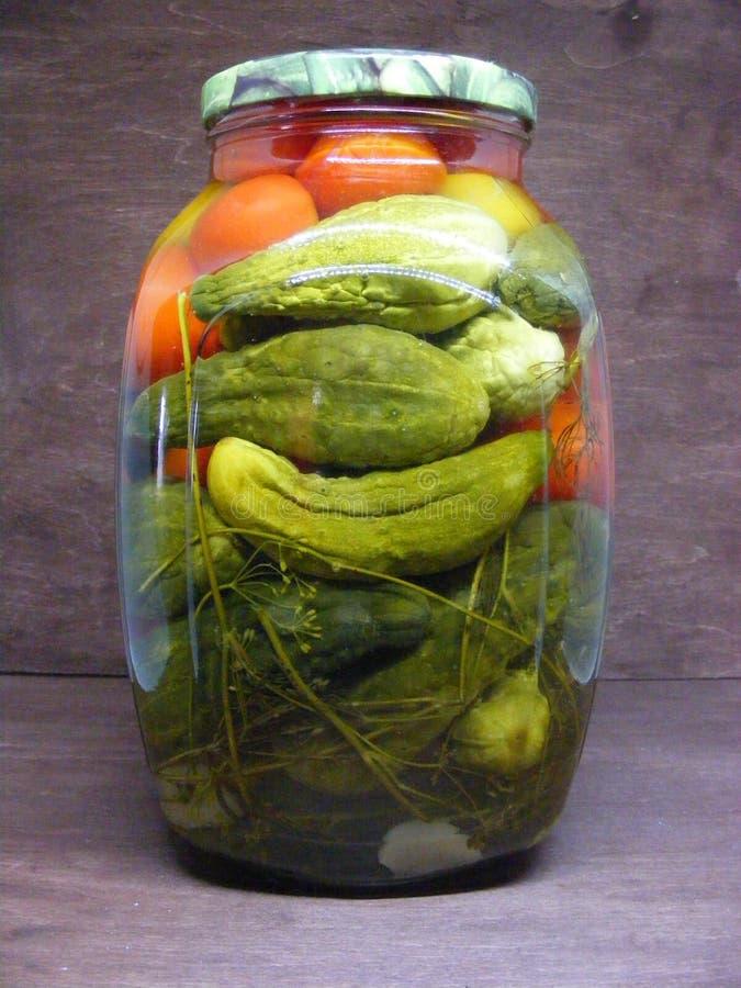 瓶子杯黄瓜和蕃茄,传统俄语保存 免版税库存照片