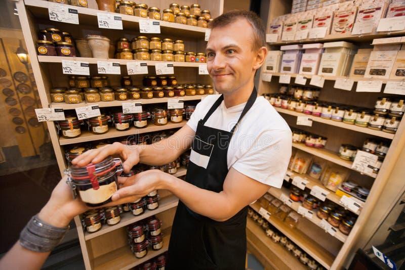 给瓶子果酱的推销员女性顾客在杂货店 免版税库存照片