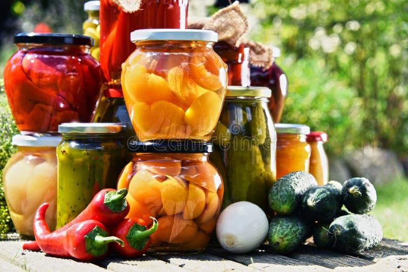 瓶子泡菜和果子在庭院里 免版税库存照片