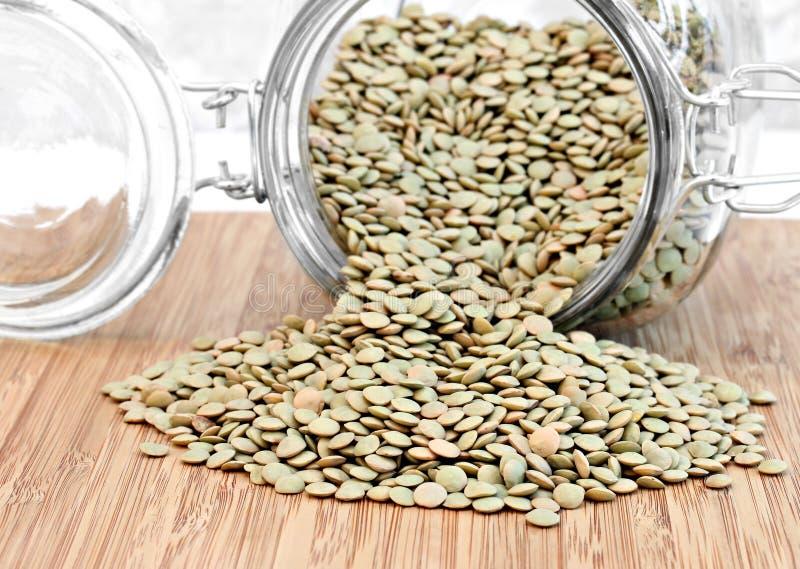 从瓶子溢出的健康绿色扁豆豆。 库存图片
