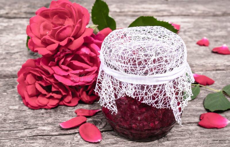 瓶子玫瑰花瓣果酱在一张木桌上的与玫瑰花  花蜜饯 r 库存图片