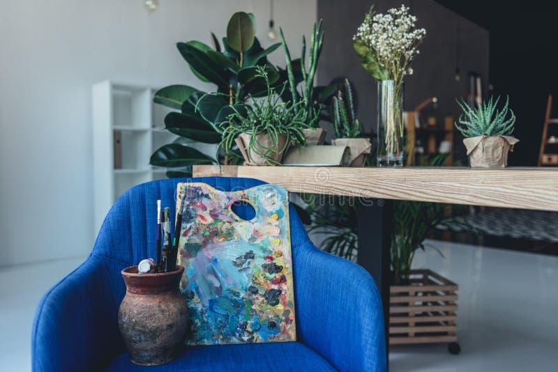 瓶子用填装了停留在蓝色扶手椅子的艺术家画笔和调色板 库存照片
