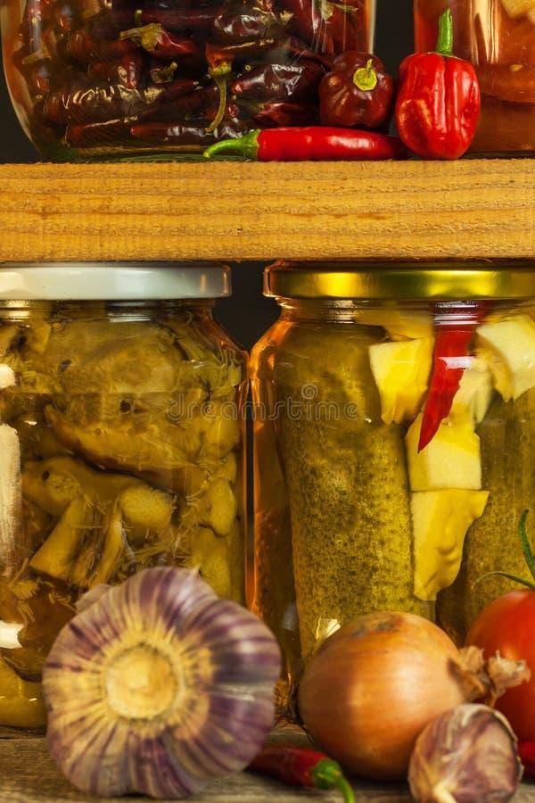 瓶子用用卤汁泡的食物和有机未加工的蔬菜 在木背景的被保存的菜 各种各样的用卤汁泡的食物 在a的生活 库存照片