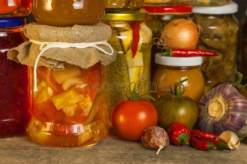 瓶子用用卤汁泡的食物和有机未加工的蔬菜 在木背景的被保存的菜 各种各样的用卤汁泡的食物 在a的生活 图库摄影
