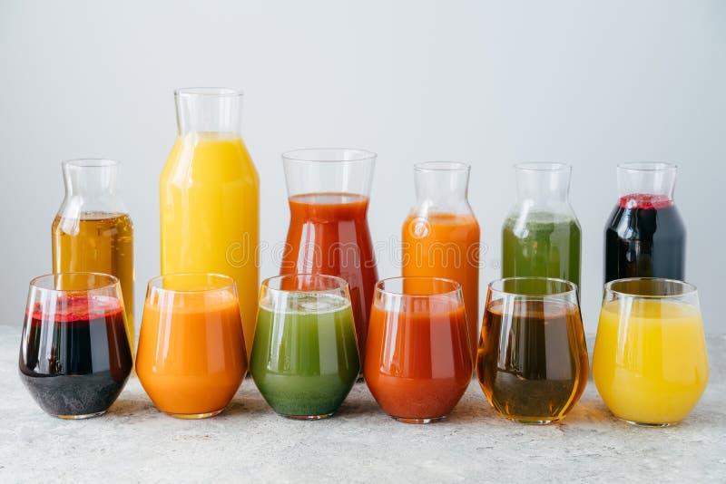 瓶子的分类用鲜美多彩多姿的汁液,在桌上站立反对白色背景 非酒精饮料 夏天饮料 图库摄影