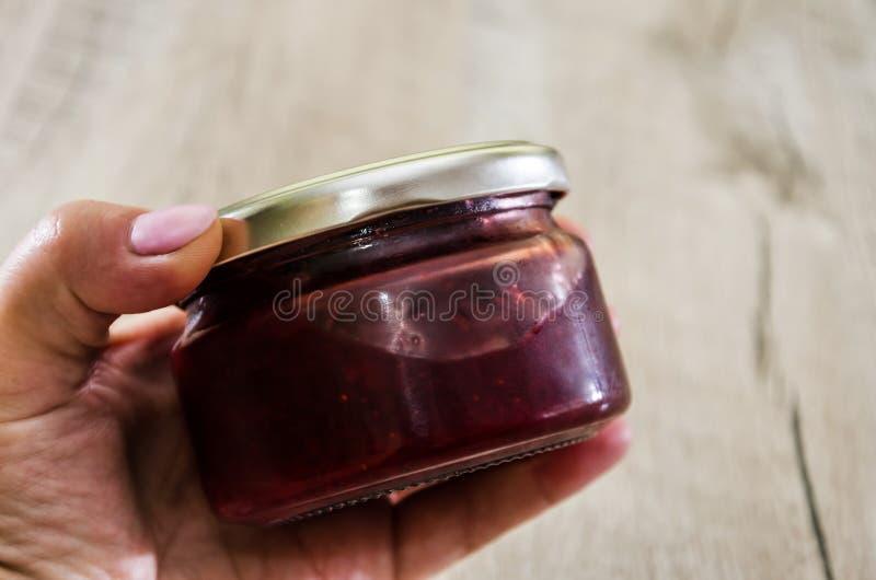 瓶子草莓酱在手中在木背景 r 免版税库存图片