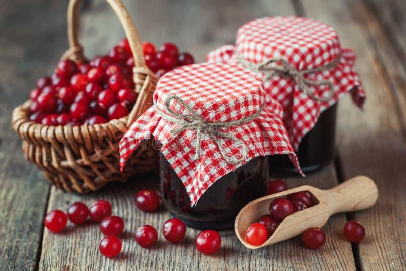 瓶子蔓越桔阻塞和篮子用沼泽莓果 免版税库存图片