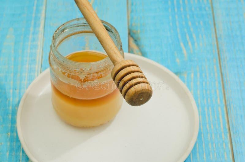 瓶子蜂蜜和蜂蜜浸染工在一个白色碗在一张蓝色木桌上 图库摄影