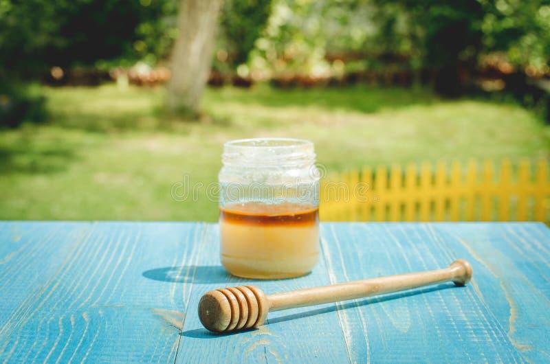 瓶子蜂蜜和蜂蜜浸染工在一张蓝色木桌上在庭院里 免版税库存照片