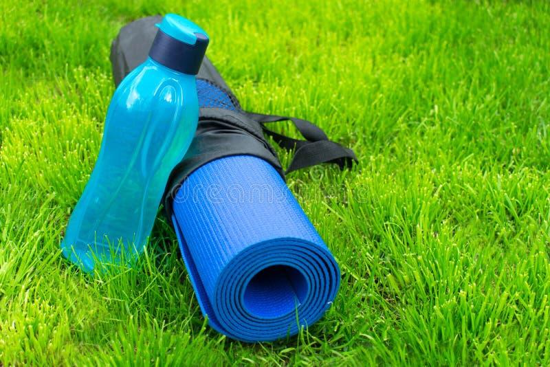 瓶或水在瑜伽席子在新鲜的绿草 训练和休闲的概念 体育和健康 健康,饮食,ene 免版税库存照片