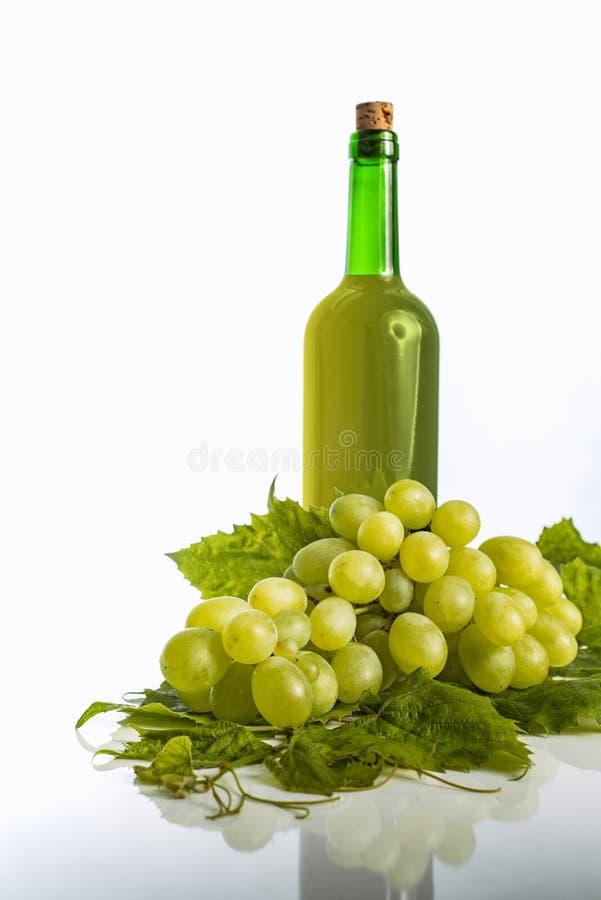 瓶新鲜的白葡萄酒用在白色的葡萄 库存图片