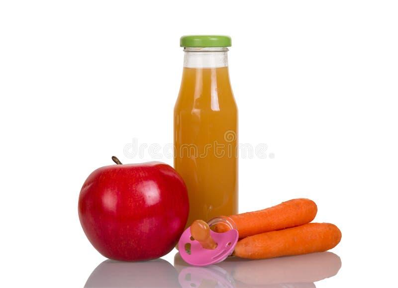 瓶果汁,在白色隔绝的苹果计算机、红萝卜和婴孩安慰者 库存照片