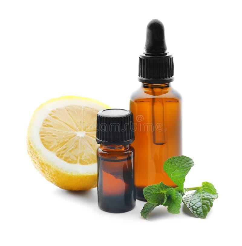 瓶柑橘精油、薄荷叶和柠檬在白色背景 免版税库存图片