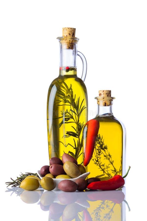 瓶橄榄油用胡椒和草本在白色 库存图片