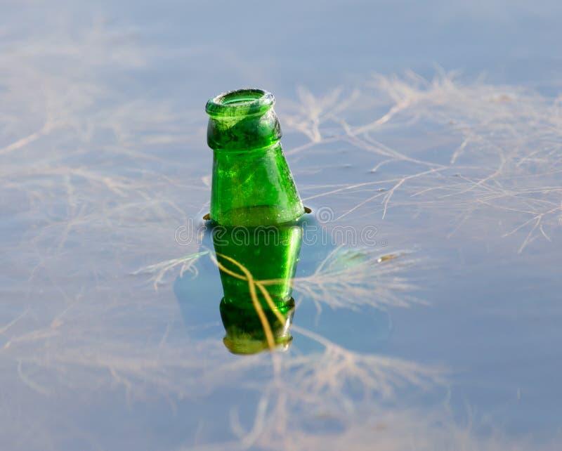 瓶水在湖 免版税库存图片