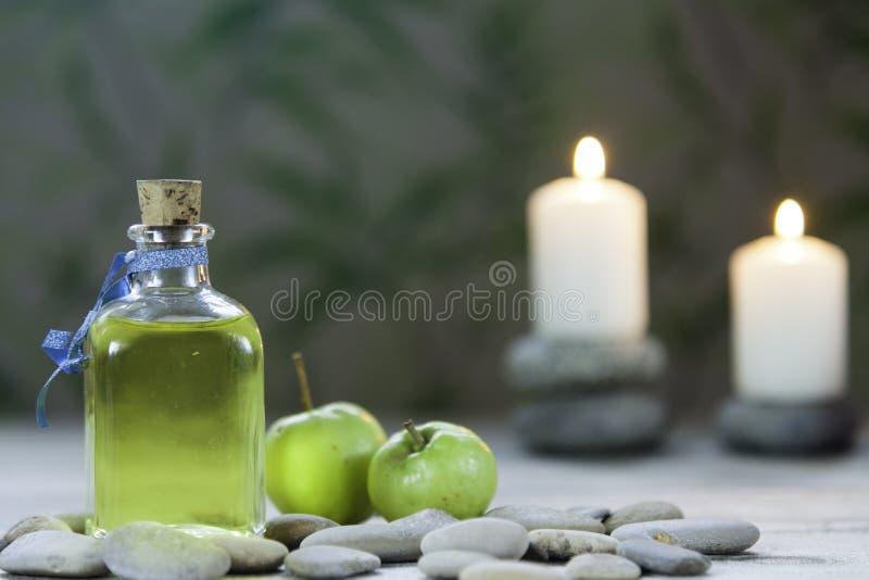 瓶油按摩、河小卵石、两个小绿色苹果和两个被点燃的蜡烛在木桌和草本背景上 免版税图库摄影
