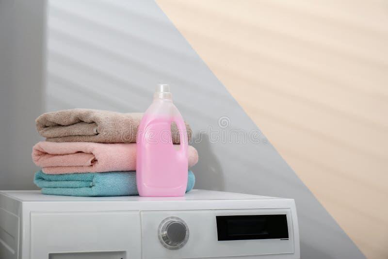 瓶洗涤剂和在户内洗衣机的清洁毛巾 免版税图库摄影