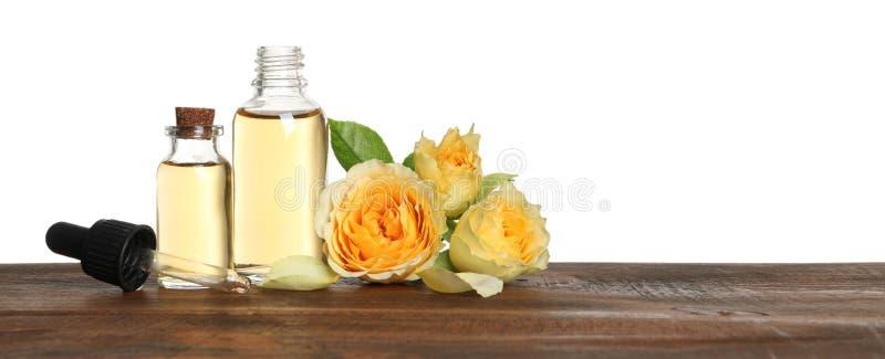 瓶玫瑰色精油和花,白色背景 免版税库存照片