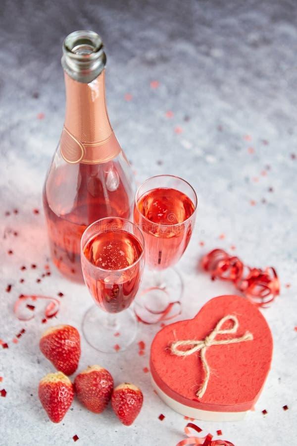 瓶玫瑰色香槟、玻璃用新鲜的草莓和心形的礼物 免版税库存图片