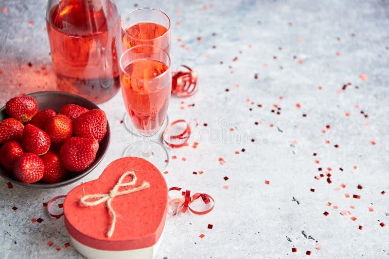 瓶玫瑰色香槟、玻璃用新鲜的草莓和心形的礼物 库存照片