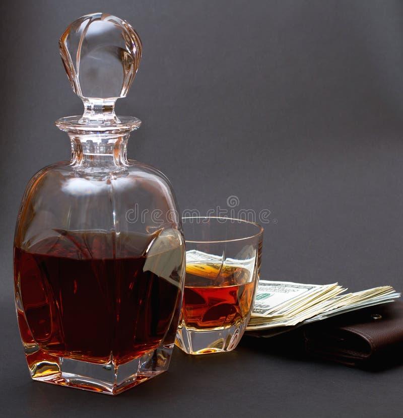 瓶用威士忌酒和一块玻璃用威士忌酒和批金钱在一个棕色钱包 库存照片