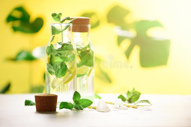 瓶用戒毒所水的薄菏、柠檬和热带monstera叶子在黄色背景 柑橘柠檬水 美满的果子石榴红色种子夏天 免版税库存图片