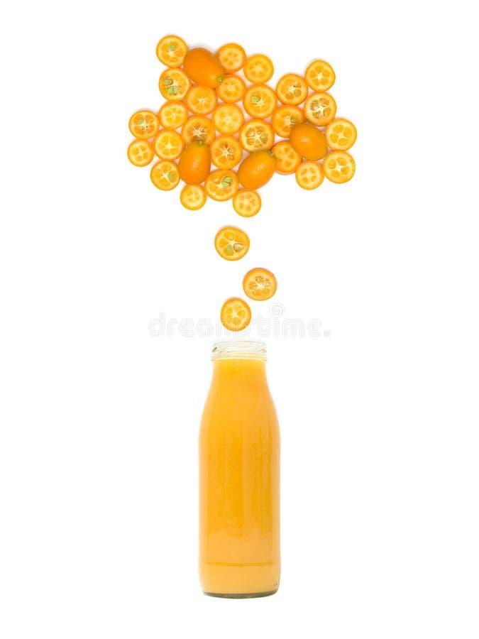 瓶用新鲜的金桔汁站立在白色背景的许多金桔切片下 免版税库存照片
